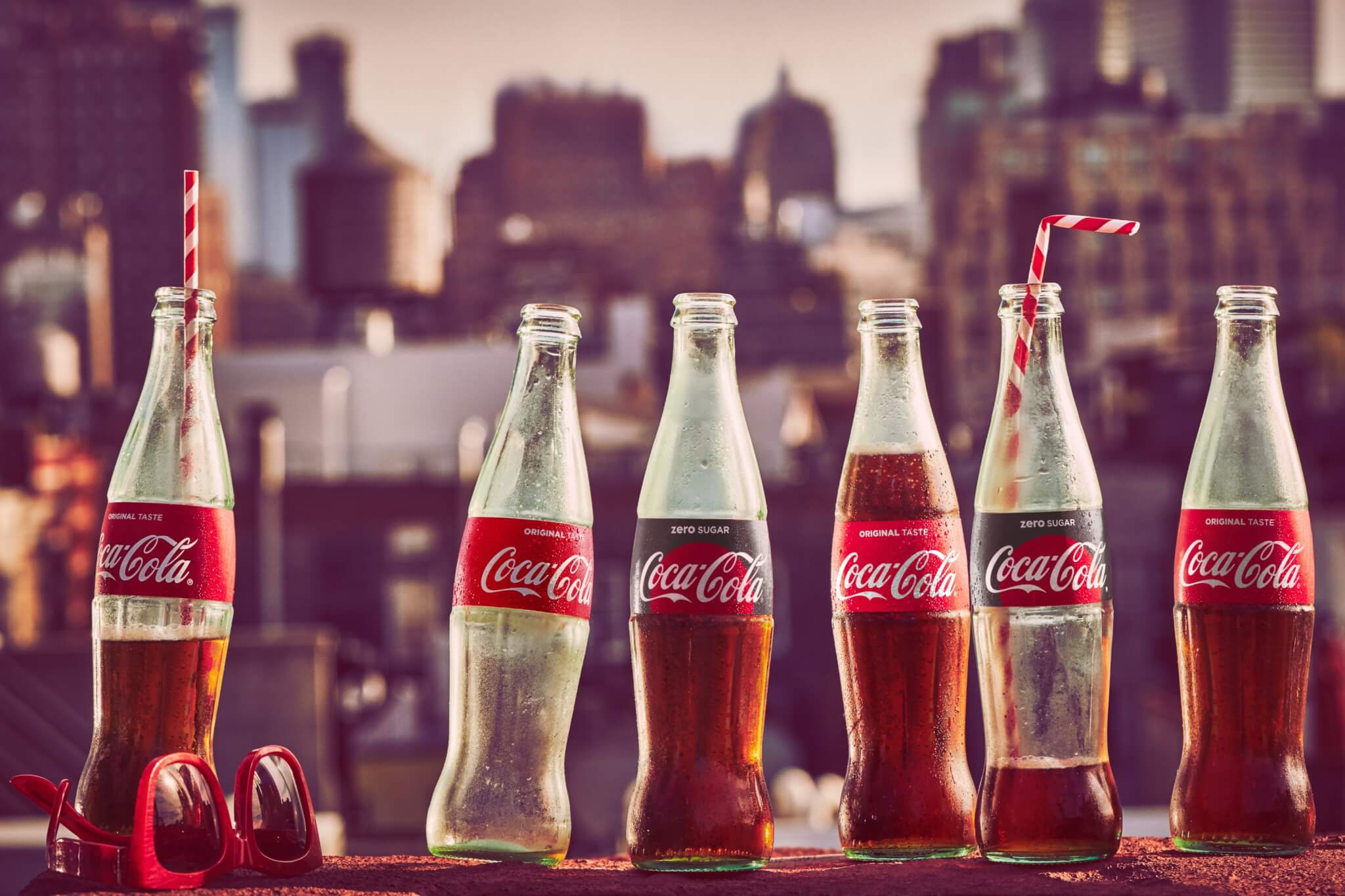 Coca-Cola glass bottles set against a skyline